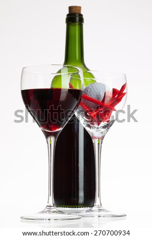 Wine glasses with red wine and golf ball on white table - stock photo