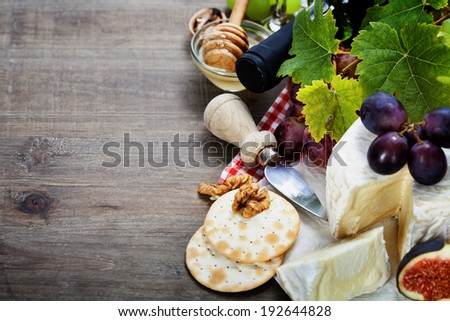 Wine, grape and cheese on wooden background - stock photo