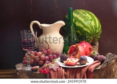 Wine, grapes, a pomegranate, a fig, a water-melon and a white jug - stock photo
