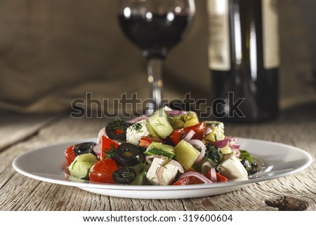 Wine. Greek salad. Small dish. Vegetables on a wooden table. Wine in a glass and a bottle of wine. Rustic style.