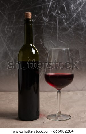 Wine in a glass with a bottle on the background