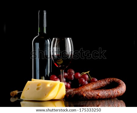 Wine in bottle and glass, grapes, cheese an sausage on black background