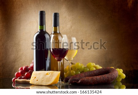 Wine in bottles and glasses, grapes, cheese an sausage on linen background