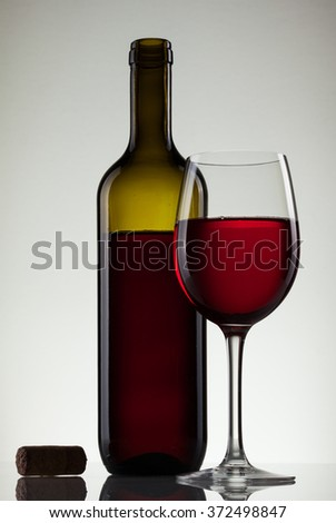 Wine in glass and bottle of wine on white