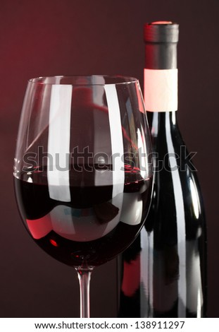 Wine in glass and wine bottle close-up on dark background
