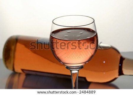 Wine in glass with bottle behind it - stock photo