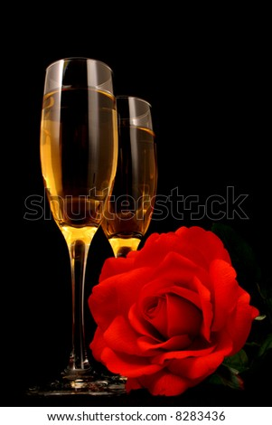 Wine in glasses with a rose all on a black background with mood lighting - stock photo