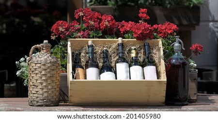 Wine in old bottles on a barrel. - stock photo