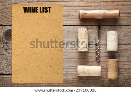 Wine list and corks with corkscrew on wooden background - stock photo