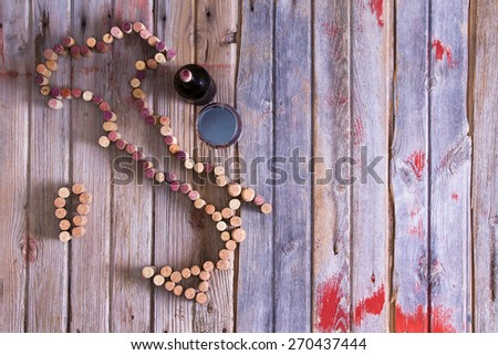Wine lovers map of Italy formed from used red and white wine corks with a bottle and glass of red wine alongside on rustic wooden boards with copy space, overhead view - stock photo