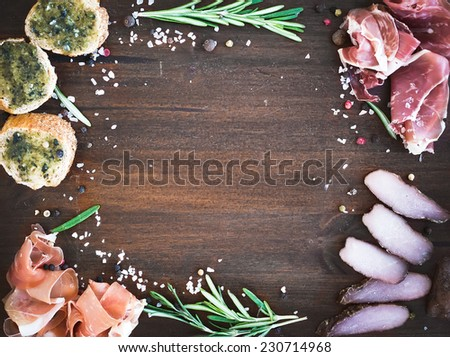 Wine meat appetizer set: prosciutto, serrano and cured lamb meat selection with spices, herbs and baguette slices with pesto on a dark wood background with a copy space in the center - stock photo
