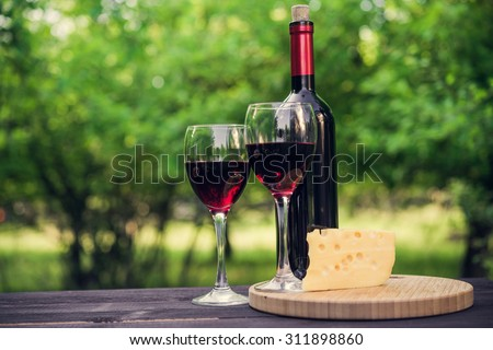Wine of bottle and glass on wood table. piece of cheese. - stock photo