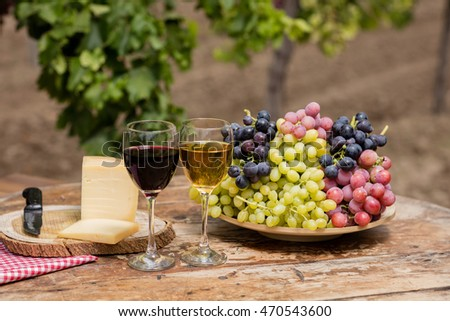 Wine on rustic wood table in vineyard.