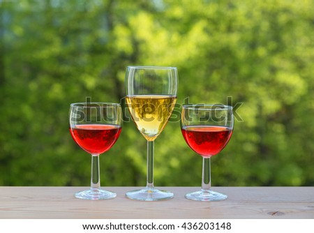 wine party outdoors. three wine glasses on table in the garden