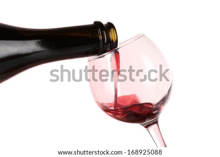 Wine poured into glass on pink background - stock photo