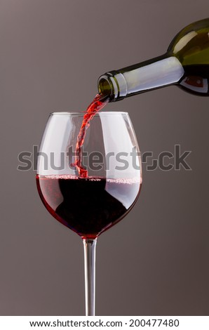 Wine pouring in glass on grey background