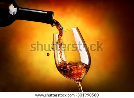 Wine pouring in wineglass on an orange background - stock photo