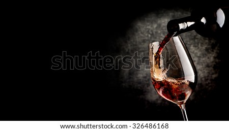 Wine pouring in wineglass on the black background - stock photo