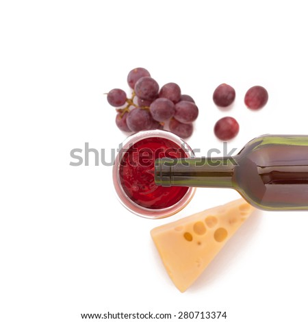 Wine pouring into wine glass, close-up. Cheese, grapes and wine bottles on white background. Flat mock up for design. Top view - stock photo