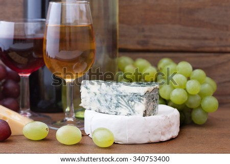 Wine pouring into wine glass, close-up. Cheese, grapes and wine bottles on wooden table in restaurant. Flat mock up for design  - stock photo