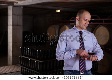 Wine producer inspecting quality of red wine, standing in front of barrels in cellar