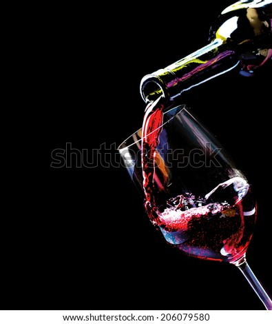 Wine. Red wine pouring into a wine glass. Isolated on black background. Border art design - stock photo