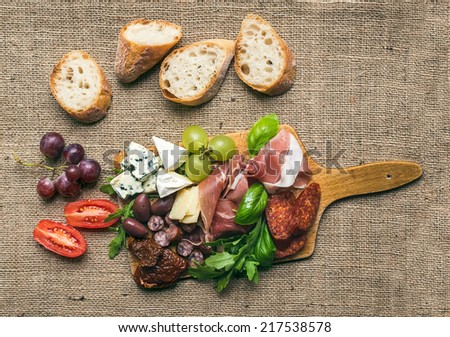 Wine set consisting of smoked meat, sausages, cheese, grapes, cherry-tomatoes, olives,  basil leaves, arugula, dried tomatoes and baguette slices on a rustic wood board over the hessian background - stock photo