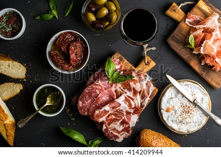 Wine snack set. Glass of red, meat selection, mediterranean olives, sun-dried tomatoes, baguette slices, camembert cheese and spices on black background, top view - stock photo