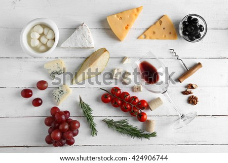 Wine, snacks and different various of cheese, flat lay - stock photo