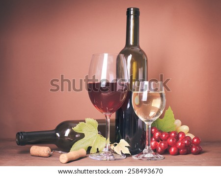 Wine still life: bottles, corks, grapes and glasses - stock photo