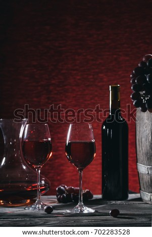 Wine still life with wine in glasses and grapes on a wooden table. Toning.