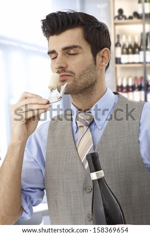 Wine-taster smelling cork eyes closed after opening bottle of wine. - stock photo