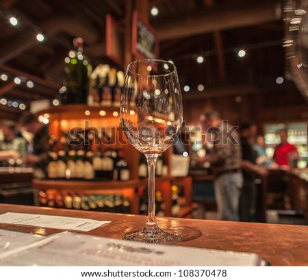 Wine tasting at Napa Valley. The glass was empty and ready for the next one. Bartender was at the bar. Photo taken with low speed. - stock photo