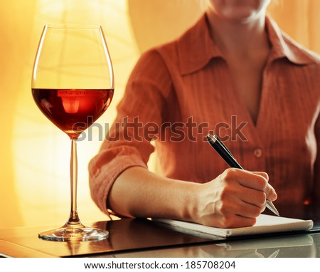 Wine tasting. Sommelier making notes in notebook. - stock photo