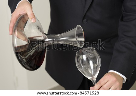 Wine waiter decantering a bottle of red wine - stock photo