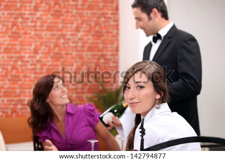 wine waiter showing a sparkling wine bottle to customers