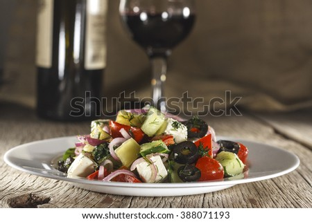 Wine. Wine in a glass and bottle on a wooden table, closeup, country style. Greek salad on white plate