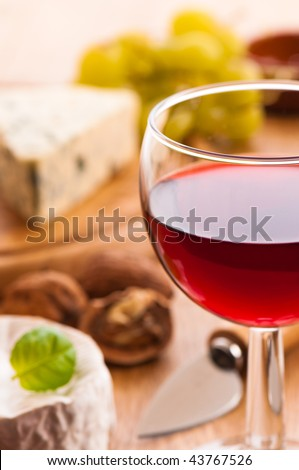 Wine with cheese selection in background - focus on rim of glass - shallow depth of field