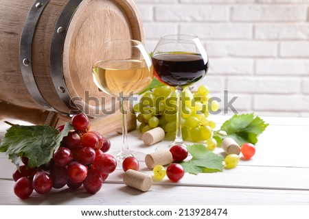 Wine with grapes on table on brick wall background - stock photo