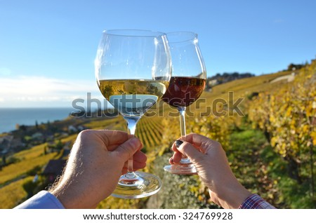Wineglases in the hands against vineyards in Lavaux region, Switzerland - stock photo
