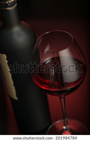 Wineglass and bottle, dark-red background
