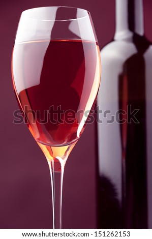 wineglass and bottle of rose wine against warm colored background
