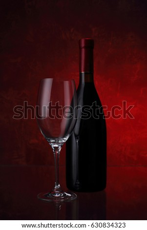 Wineglass and bottle with red wine on red background