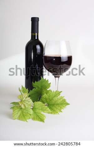wineglass, bottle of wine and grapes leaf - stock photo