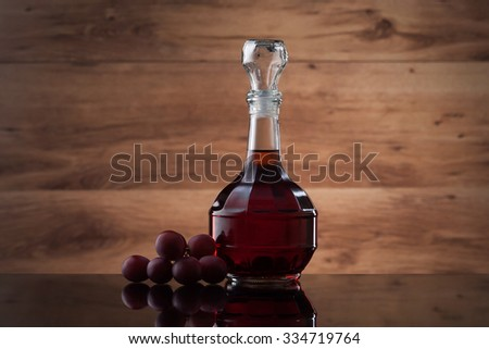 Wineglass, carafe of wine and red grapes on wooden texture - stock photo