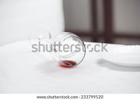 Wineglass fallen to the white tablecloth - stock photo