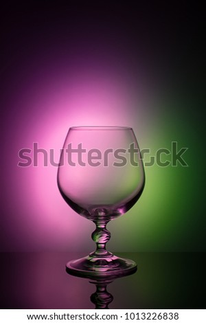 Wineglass on a color background with a black vignette. A tall Wineglass with a thin stalk