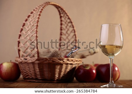 Wineglass on wooden table and bottle of white wine and corkscrew in basket - stock photo