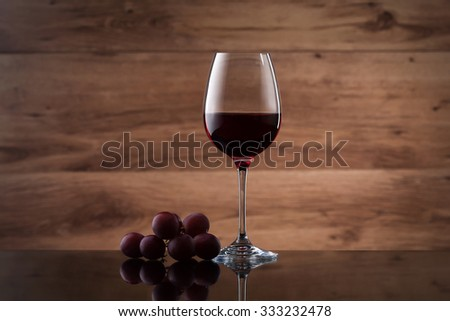 Wineglass, with red  wine and red grapes isolated on wooden texture - stock photo