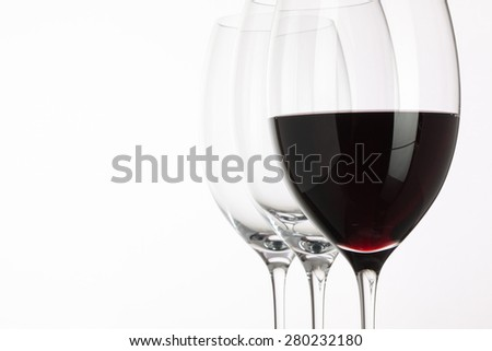 Wineglass with red  wine on a white background - stock photo
